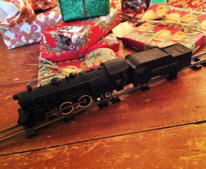 An antique train, presents, and a tree skirt adorn my tree